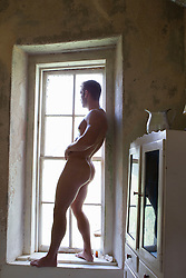 naked bodybuilder with a bubble butt ass standing on a window ledge indoors