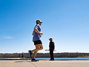 19 APRIL 2020 - DES MOINES, IOWA: People jog and walk around Gray's Lake, a popular public park and lake south of downtown Des Moines. After a week of colder than normal weather, including three inches of snow, the weekend was spring like and people went to public parks to enjoy the pleasant weather.        PHOTO BY JACK KURTZ