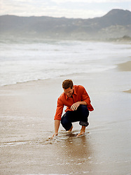 man squatting down to feel the Pacific Ocean in Southern California