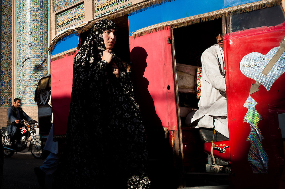 A young woman walks down one of the bazaar streets of Herat as a tuk-tuk driver glares at her from his driver's seat.