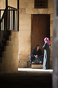 Two women talk in an alleyway, Bein al-Qasreen area, Islamic Cairo, Cairo, Egypt