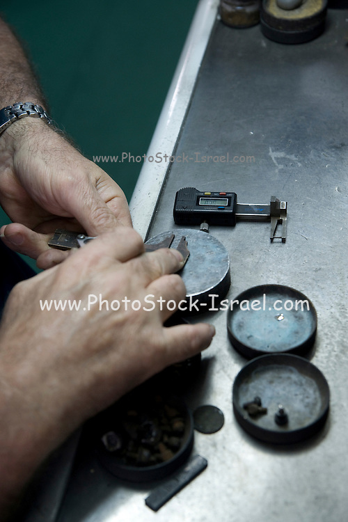 Israel, Interior of a diamond cutting and polishing workshop. A workers work station a worker inspecting and measuring the stones