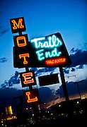 """SHOT 8/7/09 8:25:21 PM - The neon sign for the Trails End Motel in Lakewood, Co. on West Colfax Avenue. Colfax Avenue is the main street that runs east and west through the Denver-Aurora metropolitan area in Colorado. As U.S. Highway 40, it was one of two principal highways serving Denver before the Interstate Highway System was constructed. In the local street system, it lies 15 blocks north of the zero point (Ellsworth Avenue, one block south of 1st Avenue). For that reason it would normally be known as """"15th Avenue"""" but the street was named for the 19th-century politician Schuyler Colfax. On the east it passes through the city of Aurora, then Denver, and on the west, through Lakewood and the southern part of Golden. Colloquially, the arterial is referred to simply as """"Colfax"""", a name that has become associated with prostitution, crime, and a dense concentration of liquor stores and inexpensive bars. Playboy magazine once called Colfax """"the longest, wickedest street in America."""" However, such activities are actually isolated to short stretches of the 26-mile (42 km) length of the street. Periodically, Colfax undergoes redevelopment by the municipalities along its course that bring in new housing, trendy businesses and restaurants. Some say that these new developments detract from the character of Colfax, while others worry that they cause gentrification and bring increased traffic to the area. (Photo by Marc Piscotty / © 2009)"""