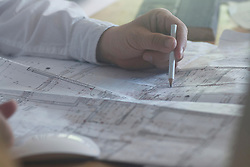 Cropped image of a businessman with pencil working on blueprint in the office, Freiburg im Breisgau, Baden-Wuerttemberg, Germany