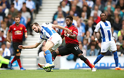 Brighton & Hove Albion's Tomer Hemed (centre) and Manchester United's Fred battle for the ball