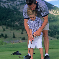 A father teaches his son to putt on a golf course at Big Sky, Montana.