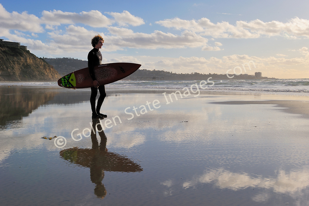 Surfers reflection on the tidal flats late afternoon light. La Jolla in the background. (Not Model Released)