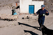 Bolivia,  June 2013. Choritotoro, village on the altiplano. Angel spinning wool , unusual for a man, and Maria with her sheep.