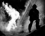 A fireman moves away from a burst of flame atop a West Seattle house. (Matt McVay / The Seattle Times, 1979)