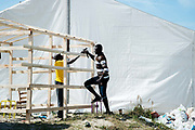 Calais August 2015 The Jungle, camp of migrants, most of whom are trying to get to England. Two men from Sudan construct a shelter.