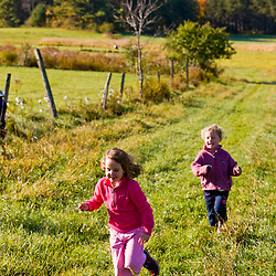 Kids play in a hay field at the Clark Farm in Windham, Maine.