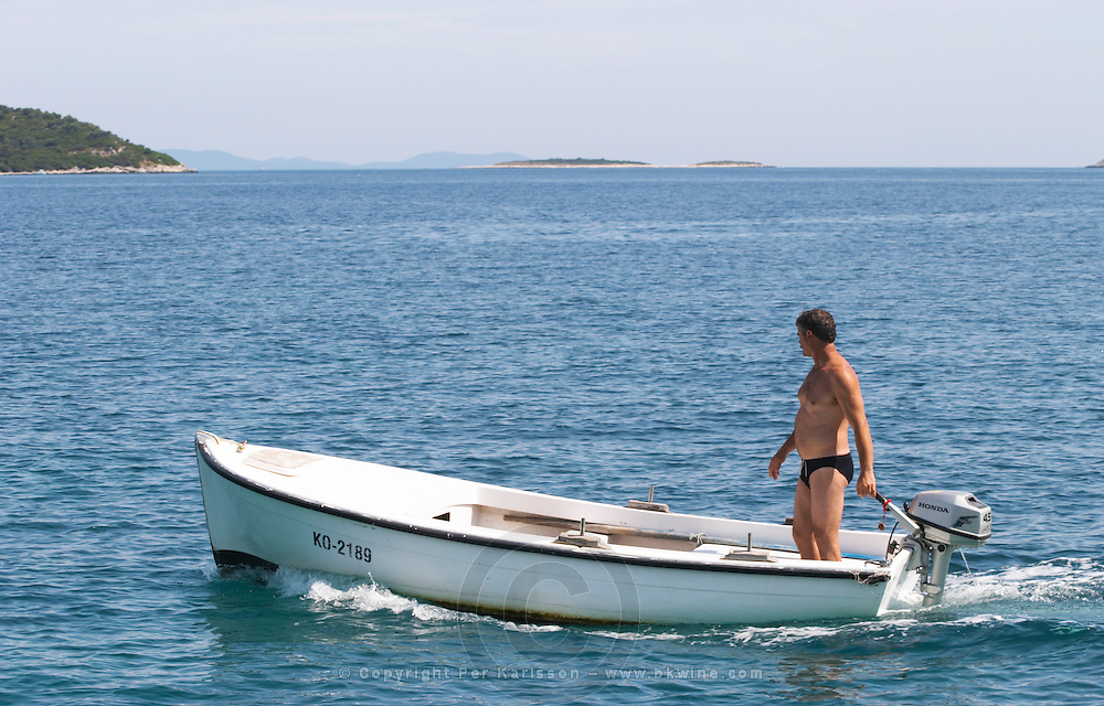 A man standing in a small boat with a Honda outboard motor on the blue sea, islands in the background Orebic town, holiday resort on the south coast of the Peljesac peninsula. Orebic town. Peljesac peninsula. Dalmatian Coast, Croatia, Europe.