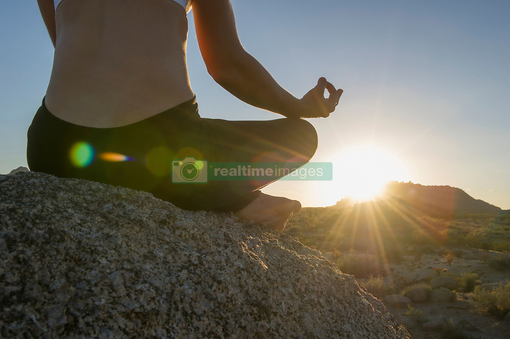 Woman sitting in lotus position on boulder at sunrise (Credit Image: © Image Source/Les & Dave Jacobs/Image Source/ZUMAPRESS.com)