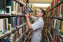 Man with hearing impairment in university library.