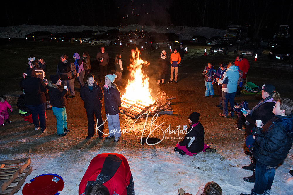 Sledders warmed up with hot chocolate by the bonfire during Laconia Parks and Rec's Sledding Party on Friday evening.  (Karen Bobotas/for the Laconia Daily Sun)