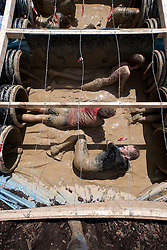 © Licensed to London News Pictures. 12/05/2012. Kettering, UK. Mud soaked Tough Mudder competitors work their way through a challenge which consisted of crawling through two sets of long pipes and underneath barbed wire. Thousands of people took part in Tough Mudder today (12/05) in the grounds of Boughton House, Northamptonshire. The 12 mile course which was designed by British special forces soldiers, consisted of 25 extreme obstacles including water, mud, electrocution, and high walls. The challenge is designed to test teamwork abilities as well as physical strength and stamina . Photo credit : James Gourley/LNP