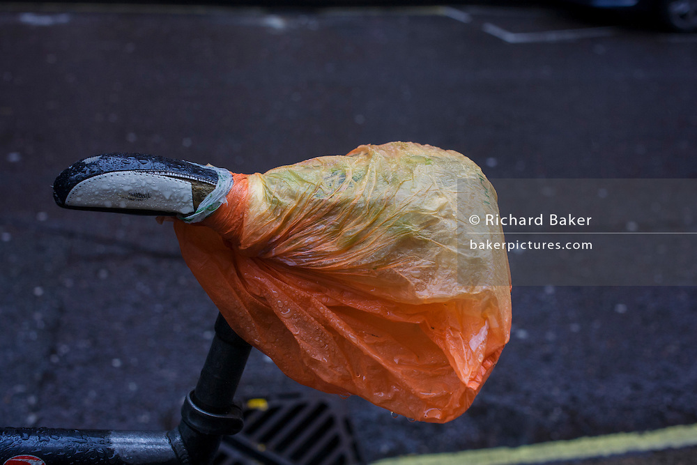A wet saddle partly covered by a plastic bag in a central London street.