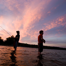 Two men fishing at sunset on Lake Sunapee at Mount Sunapee State Park in Newbury, New Hampshire.