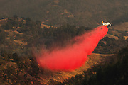 HEALDSBURG, CA - OCTOBER 26: An air tanker drops fire retardant in the valley below during the firefighting operations to battle the Kincade Fire in Healdsburg, California on October 26, 2019. (Photo by Philip Pacheco/AFP)