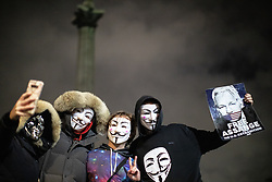 "© Licensed to London News Pictures . 05/11/2019. London, UK. A man holds "" Free Assange "" poster as other take a selfie in front of Nelson's Column in Trafalgar Square . Supporters of Anonymous , many wearing Guy Fawkes masks , attend the Million Mask March bonfire night demonstration , in Trafalgar Square in central London . Photo credit: Joel Goodman/LNP"