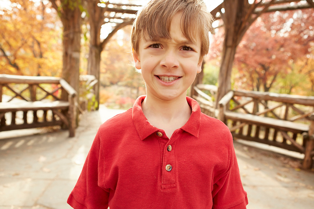 Lifestyle image of frowning boy outside in park during autumn