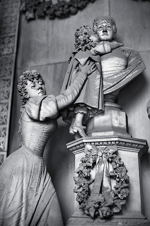 """Picture and image of the late borgeoise realistic style stone sculpture of the Gallino tomb sculpted by  G. Moreno 1894.  In the tomb, the bust that portrays the deceased Carolina receives the kiss of a child, probably the niece, supported by a young woman - the mother, or perhaps the elder sister - whose face is marked by pain; on the right an older man, presumably her husband, stands aside, almost absent, looking down at the ground. The most intimate tones and psychological introspection are grafted here in the language of bourgeois Realism: with undoubted technical virtuosity Moreno offers a rigorous """"quantitative"""" description of reality, dwelling on every single detail of faces, clothing, accessories and hairstyles . Section A, no 54, The monumental tombs of the Staglieno Monumental Cemetery, Genoa, Italy .<br /> <br /> Visit our PEOPLE & PLACES PHOTO ART COLLECTIONS for more photos to buy as buy as wall art prints https://www.photoshelter.com/mem/images/index#/C00001WetsxVxNTo/ .<br /> <br /> Visit our LANDSCAPE PHOTO ART PRINT COLLECTIONS for more wall art photos to browse https://funkystock.photoshelter.com/gallery-collection/Places-Landscape-Photo-art-Prints-by-Photographer-Paul-Williams/C00001WetsxVxNTo"""