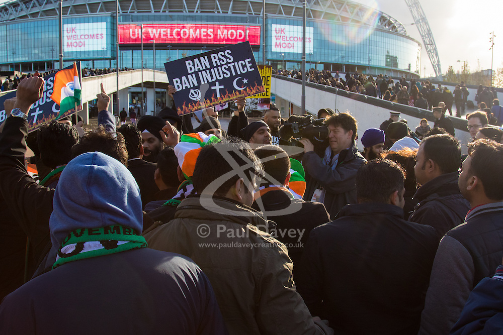 As a small group of Sikh  protesters demonstrate outside Wembley Stadium, thousands of the UK's Indian community stream into the stadium ahead of an address to more than 60,000 by Indian Prime Minister Narendra Modi at a 'UK Welcomes Modi' reception. With more than 9 billion worth of trade deals signed during his visit, the euphoria is tempered by the fact that just a few years ago he was a persona non grata in the UK. Modi, a Hindu and his BJP party are accused of a wide range of human rights abuses against religious and ethnic minorities in India. PICTURED: Modi supporters chant as a small group of Sikh protesters demonstrate outside the stadium. ©2015 Paul Davey. All rights reserved.   // Licensing: Please contact Paul Davey paul@pauldaveycreative.co.uk Tel +44 (0) 7966 016 296 or +44 (0) 208 969 6875.