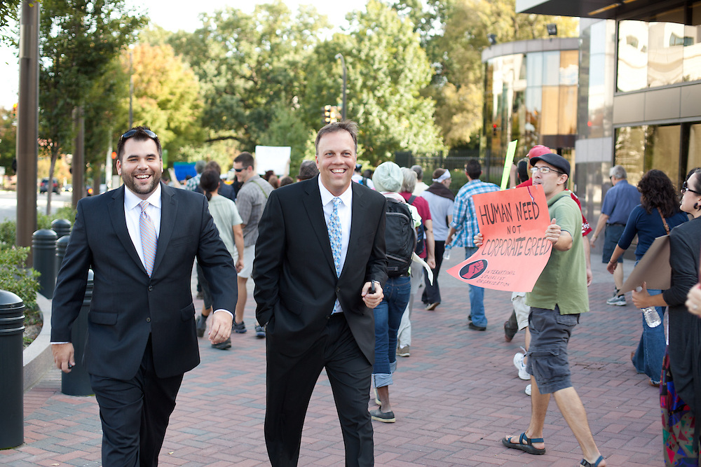 Two man in suits pass the large group of protestors on the way back from demonstrating in front of BOA headquarters in uptown Charlotte, NC.