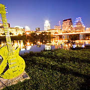 View of downtown Austin from Riverside, across Town Lake with one of the painted Austin City Limits guitars in the foreground.