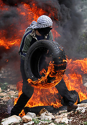 Feb. 17, 2017  - Nablus, West Bank - A Palestinian protester burns a tire during clashes after a protest against the expanding of Jewish settlements in Kufr Qadoom village in the West Bank. (Credit Image: © Xinhua via ZUMA Wire)