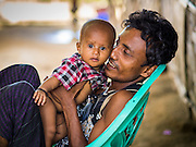 06 NOVEMBER 2014 - SITTWE, RAKHINE, MYANMAR: ZAW ZAW HLAING, 27, and his daughter, HOWEVER, 6 months, play in a Rohingya Muslim IDP camp near Sittwe. After sectarian violence devastated Rohingya communities and left hundreds of Rohingya dead in 2012, the government of Myanmar forced more than 140,000 Rohingya Muslims who used to live in and around Sittwe, Myanmar, into squalid Internal Displaced Persons camps. The camps are about 20 minutes from Sittwe but the Rohingya who live in the camps are not allowed to leave without government permission. The government says the Rohingya are not Burmese citizens, that they are illegal immigrants from Bangladesh. The Bangladesh government says the Rohingya are Burmese and the Rohingya insist that they have lived in Burma for generations. They are not allowed to work outside the camps, they are not allowed to go to Sittwe to use the hospital, go to school or do business. The camps have no electricity. Water is delivered through community wells. There are small schools funded by NOGs in the camps and a few private clinics but medical care is costly and not reliable.   PHOTO BY JACK KURTZ