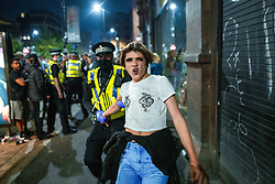 © Licensed to London News Pictures . 07/07/2021. Manchester, UK. Police detain people after some climbed on to the rooves of bus shelters as fans and revellers pack in to Stevenson Square in Manchester City Centre as celebrations take place following Englands victory over Denmark in the European Cup secured the team a place in the cup final . Photo credit: Joel Goodman/LNP