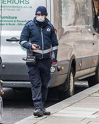© Licensed to London News Pictures. 19/03/2020. London, UK. A Westminster traffic warden wears a protective masks while checking parked cars as London prepares to shutdown over the Coronavirus pandemic crisis. Photo credit: Alex Lentati/LNP