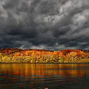 """""""On the Move""""<br /> <br /> Awesome dark storm clouds combined with bits of sunlight move quickly across the sky. Beautiful fall foliage becomes illuminated, and reflected on to the waters below!<br /> <br /> Autumn Landscapes by Rachel Cohen"""