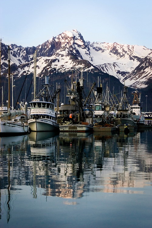 Fishing boats, Seward, Alaska, on reflective evening water, and the mountains behind.
