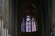 The Reims Cathedral: the stained glass windows behind the altar, Reims, Champagne, Marne, Ardennes, France, low light grainy grain