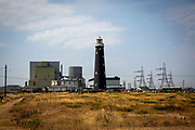The Old Lighthouse of Dungeness, Kent, United Kingdom. A Historic Grade II listed building, it is the fourth lighthouse built on Dungeness and was built in 1904. Behind the lighthouse is Dungeness Nuclear Power Station.  This is a twin reactor plant located on the headlands overlooking a nature reserve and Site of Special Scientific Interest.