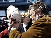 Quebec Liberal Party leader Jean Charest (R) tries to defend himself as he is hit with a whip cream pie by a protester, during a campaign stop in Blainville, Quebec with his wife Michele Dionne (C), on April 12, 2003.  REUTERS/Jim Young