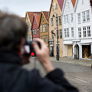 Noorwegen Bergen 30 december 2008 20081230 Foto: David Rozing .Havenstad Bergen, unesco world heritage site Bryggen. toerist maakt foto.Bryggen is de kade van de oude haven van de hanze stad Bergen. Rond de 13e eeuw werd Bergen een van de hanzesteden. Hierdoor ontstond veel handel met andere landen. Het centrum hiervan was de kade van de haven. De naam hiervoor is Bryggen. .In de 14e eeuw stonden hier zo'n 30 huizen die gedeeld werden door diverse handelsfirma's. De huizen zijn diverse keren afgebrandt en opnieuw opgebouwd. Sinds 1980 staan 58 houten gebouwen op de Unesco World Heritage lijst. .The city of Bergen, unesco world heritage site Bryggen. A tourist takes a picture.Bryggen, the old wharf of Bergen, is a reminder of the town's importance as part of the Hanseatic League's trading empire from the 14th to the mid-16th century. Many fires, the last in 1955, have ravaged the characteristic wooden houses of Bryggen. Its rebuilding has traditionally followed old patterns and methods, thus leaving its main structure preserved, which is a relic of an ancient wooden urban structure once common in Northern Europe. Today, some 62 buildings remain of this former townscape...Foto: David Rozing