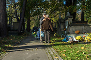 A man greets a woman with an embrace at Rakowicki Cemetery in Krakow, Poland 2019.
