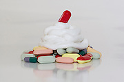 Assorted pills, medication and ointments arranged to look like a dessert. on white background