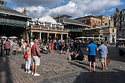 With many people and families staying in the UK for their Summer break during the school holidays, a large number of domestic tourists, who may normally have been travelling abroad, have decended on the capital to see the sights, as seen here in the plaza at Covent Garden on 10th August 2021 in London, United Kingdom. Following the Coronavirus / Covid-19 health scare of the last two years, and with some travel restrictions still in place, more people have chosen a staycation which is a holiday spent in ones home country rather than abroad, or one spent at home and involving day trips to local attractions.