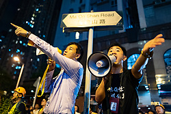 Hong Kong, China. 9th October 2019. Large peaceful crowd gathered to sing songs at MOStown mall in Ma On Shan in solidarity with several security guards who were arrested by police this week. Later small group of protestors went to nearby Shatin Divisional Police Station and shouted abuse at the police and threw objects. Riot police later charged but no arrests made. Mediators argue their case with police through megaphones. Iain Masterton/Alamy Live News.