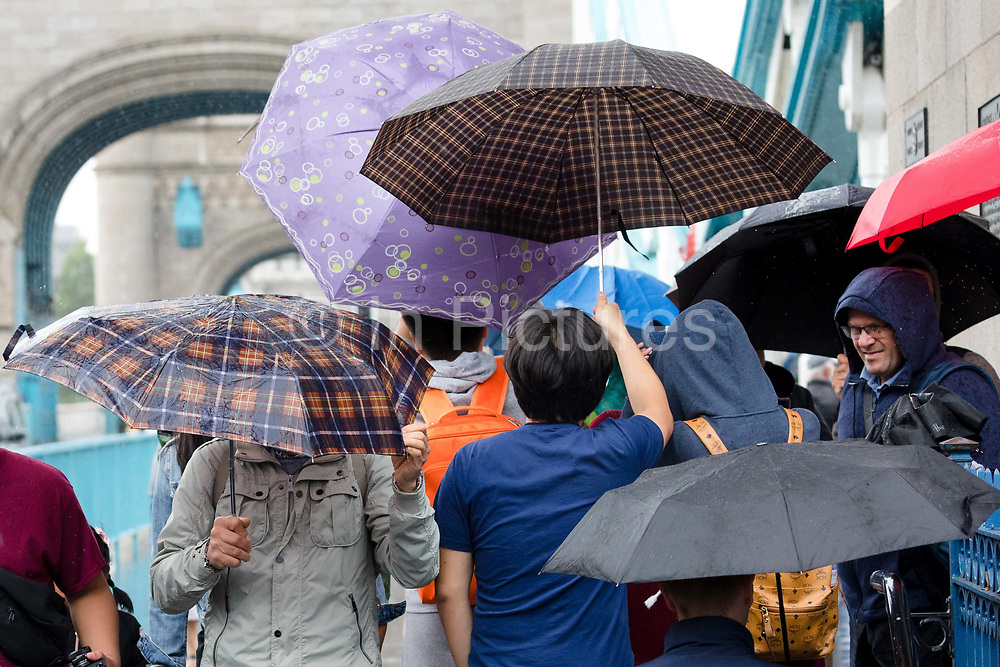 Tourists with umbrellas on Tower Bridge during rain and wet weather in London, England on August 10, 2018