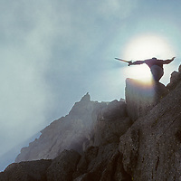 A climber greets the sun as clouds part over Mount Humphreys on the crest of California's Sierra Nevada.