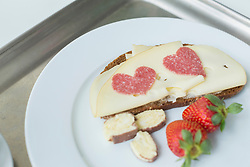 Bread with cheese, strawberry and heart shaped salami on plate, close up