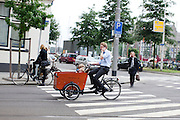 Al bellend fietst een man met twee kinderen in de bakfiets door Rotterdam, een bellende vrouw steekt over.<br /> <br /> While having a phone call a man is cycling with tow kids in a cargobike in Rotterdam. At the same time a pedestrian is crossing the street while phoning.