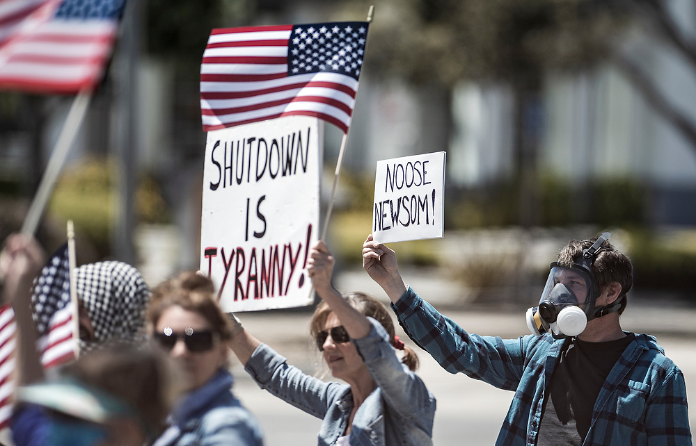A man who refused to give his name holds a sign protesting California Governor Gavin Newsom's shutdown to slow the Coronavirus pandemic during a protest at Window on the Bay park in Monterey, Calif. on May 1, 2020. About 60 people gathered to demonstrate.