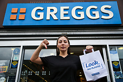 © Licensed to London News Pictures. 05/10/2021. London, UK. A woman gestures to news of the possible price increase warning as she leaves a branch of Greggs in north London. Greggs, the bakery chain, warns of price increases of sausage rolls, pasties and steak bakes following the coronavirus and supply chain crises. Photo credit: Dinendra Haria/LNP
