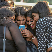 Asian girls looking at the mobile selfies at The Queen walk street Photography, on 28 June 2019, London, UK.